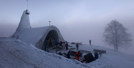 People work at the construction site of a Catholic church made of snow in the Bavarian village of Mitterfirmiansreut