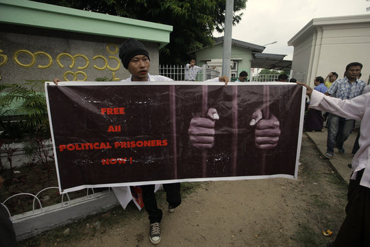 Man holds poster calling for freedom of political prisoners in front of Yangon University where U.S. President Obama was giving a speech, in Yangon