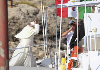 Pope Francis walks onboard a boat as he arrives at Lampedusa Island