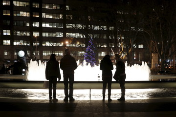 People stand next to the Revson Fountain and a Christmas tree in the background in Josie Robertson Plaza at Lincoln Center in the Manhattan borough of New York City