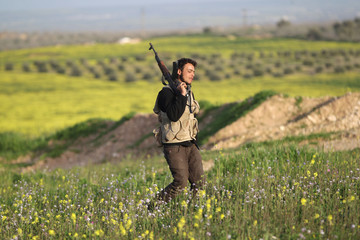 A Free Syrian Army fighter carries his weapon as he walks through a field on a frontline in Mork town