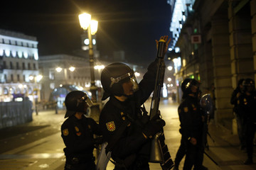 A Spanish police officers prepares to fire a rubber bullet during a 24-hour nationwide general strike in central Madrid
