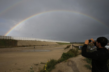 "An Afghan migrant youth uses a mobile phone to photograph a rainbow that appears near the makeshift camp called the ""Jungle"" in Calais"