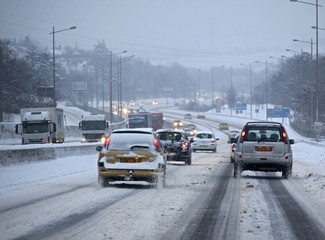 Vehicles move slowly on a snowy road near Saint-Etienne, central France