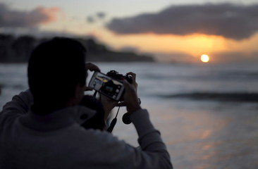 Photographs of the first sunrise of the new year are taken with a smartphone and digital camera by visitors to Australia's Bondi Beach in Sydney