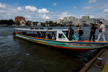 Chinese tourists board a sightseeing boat at a pier at Chao Phraya River in Bangkok