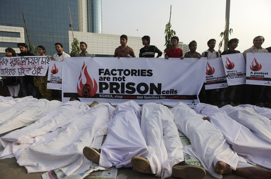 Activists of Magic Movement lie on the ground wearing traditional Muslim death robes as they stage a protest in front of Bangladesh Garment Manufacturers and Exporters Association building in Dhaka.