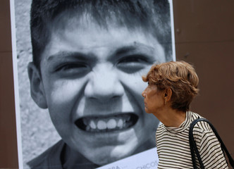 A woman looks at a poster with an images of child, which is part of an artistic project by Renaissance Foundation IAP featuring children rescued from the city's streets, in Mexico City
