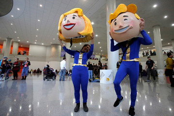Vanessa Pham and Adrian Chan remove their costumes of Vault Boy and Vault Girl at New York Comic Con in Manhattan, New York, U.S.
