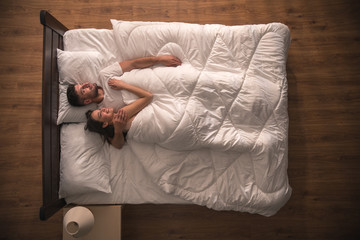 The happy lovers hug on the bed. view from above
