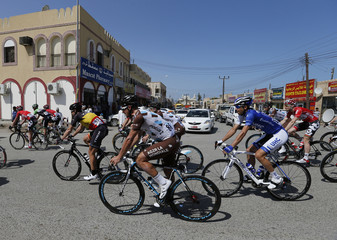 Cyclists make their way in the village of Suwayq during the start of stage one of the Tour of Oman cycling race north of Muscat