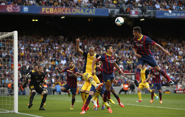Barcelona and Atletico Madrid players jump for the ball during their Spanish first division soccer match in Barcelona