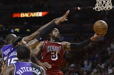 Miami Heat's Wade shoots around Sacramento Kings' Outlaw, Cousins and Patterson during their NBA basketball game in Miami