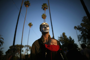 Catchings carries his sleeping son Silas during the 14th annual Dia de los Muertos festival at Hollywood Forever Cemetery in Los Angeles