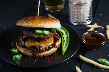 Cheeseburger with jalapeno pepper, French fries and beer