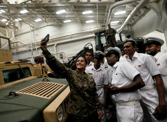 """An officer from the US Navy's """"USS New Orleans"""" vessel takes a selfie picture with Sri Lankan navy officers next to an armored vehicle during a visit at Colombo port in Sri Lanka"""