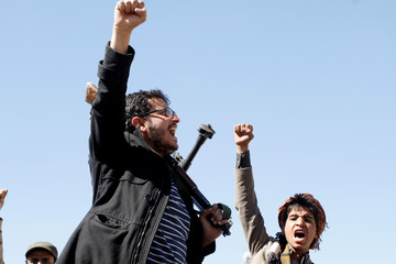 Armed tribesmen loyal to the Houthi movement shout slogans as they ride on the back of a truck during a rally held to mobilize fighters for the battles against government forces, in Sanaa