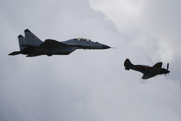 MiG-35 jet fighter and Soviet era fighter aircraft MiG-3 perform during the MAKS International Aviation and Space Salon in Zhukovsky