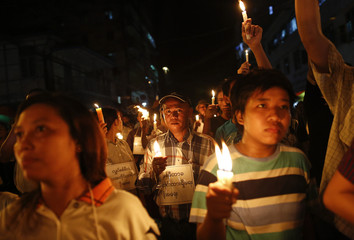 Demonstrators hold candles in a protest against the government's decision to raise electricity prices in Yangon