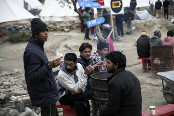 Pakistani migrants sit at a camp set by volunteers next to the Moria registration centre on the Lesbos island
