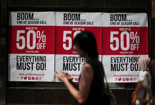 A man checks his mobile phone as he passes sale advertising in a shop window on Oxford Street in London