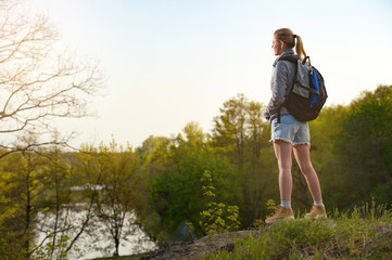 woman traveler standing on the cliff against river and blue sky