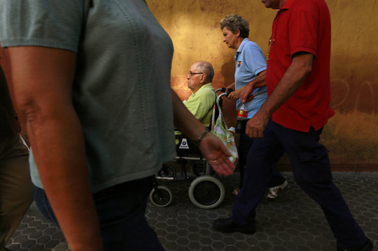 An man sitting on a wheelchair is pushed by a woman on International Day of Older Persons in the Andalusian capital of Seville