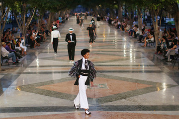 Models present creations by German designer Karl Lagerfeld as part of his latest inter-seasonal Cruise collection for fashion house Chanel at the Paseo del Prado street in Havana, Cuba