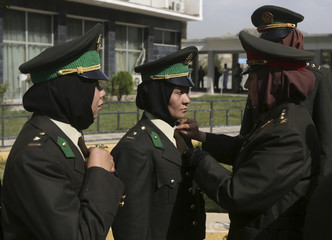 ANA officer adjusts her colleague's uniform before their graduation ceremony at the Kabul Military Training Centre