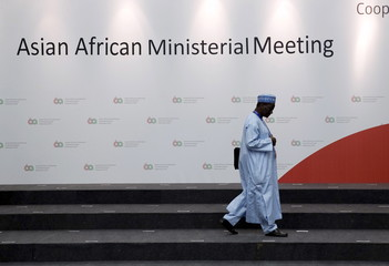A delegate to the Asian-African Conference looks at name cards for standing positions for a group photo ahead of the Ministerial meeting in Jakarta