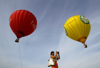 A woman takes pictures during the Taiwan International Hot Air Balloon Festival in Luye Town
