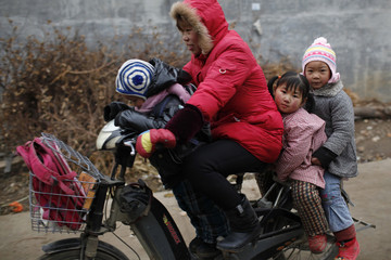 A woman rides an electric bicycle with three children outside a kindergarten in Ruzhou county