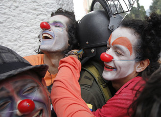 """Students hug a policeman as they march during the closing ceremony of the """"Congress for Peace"""" in Bogota"""