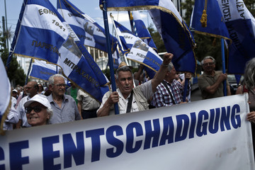 Protesters wave national flags and shout slogans during a march to the German embassy in Athens