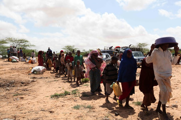 Internally displaced Somalis carry their belongings as they arrive at a newly opened camp in Madina district in Somalia's capital Mogadishu