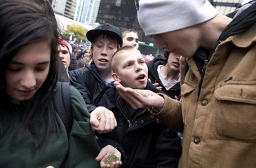 A group of friends receive a handful of free marijuana at the annual 420 marijuana rally held at the Art Gallery in Vancouver