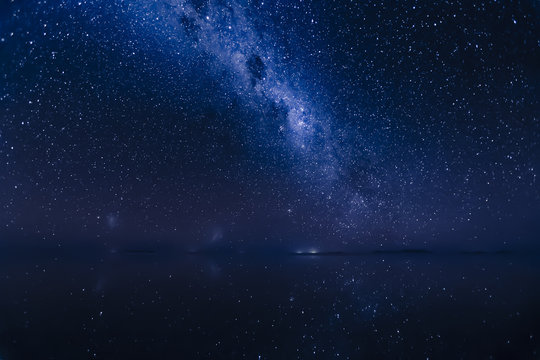 Milky Way reflects surface of water at Uyuni Salt flats in Bolivia.