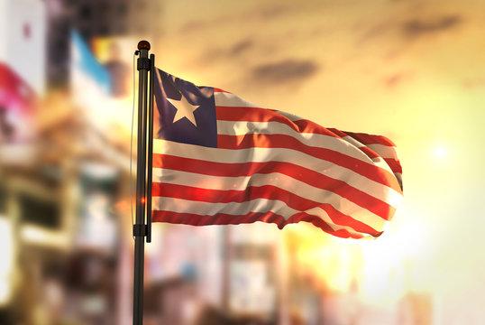 Liberia Flag Against City Blurred Background At Sunrise Backlight