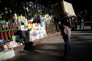 A man carrrying a box walks next to electoral posters plastered on a wall behind books on display for sale in a street of Port-au-Prince, Haiti
