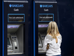A customer uses a Barclays ATM in central London