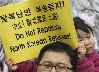 A child holds a placard during a prayer session for starving North Koreans, in Seoul