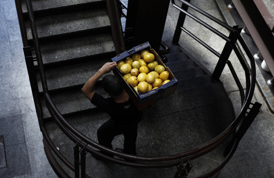 Worker carries a box of passion fruit at the Municipal Market in Sao Paulo