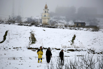 People walk down a street, with a mosque's minaret seen in the background, after snowfall on the outskirts of Medea