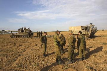 A mobile artillery unit is seen in the background as Israeli soldiers stand nearby, near the border with the Gaza Strip
