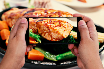 Man using smartphone take a salmon steak photo for lifestyle concept