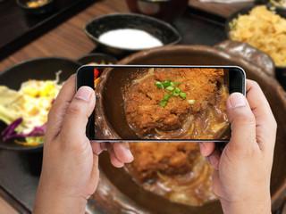 Man holding smartphone taken Tonkatsu set; Japanese food photo to share social network