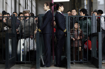 Passengers wait to have their tickets checked at Beijing Railway Station