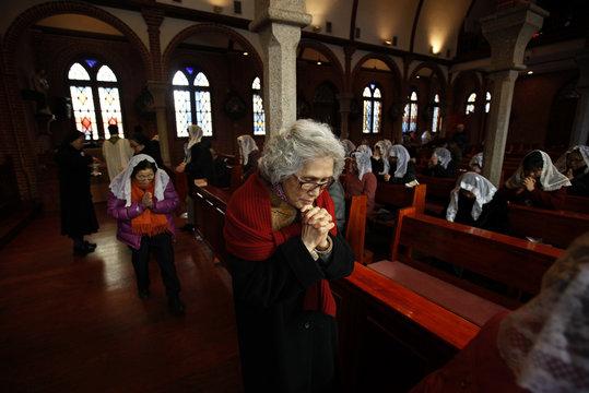 A woman prays during a mass at a catholic church in Seoul