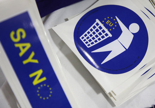 Badges with logos encouraging people to leave the EU are seen for sale on a stall at the UKIP party's spring conference, in Llandudno