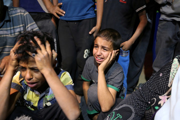 Relatives of Palestinian woman Zena Al Omor, whom hospital officials said was killed by fragments of an Israeli tank shell, mourn during her funeral in the southern Gaza Strip
